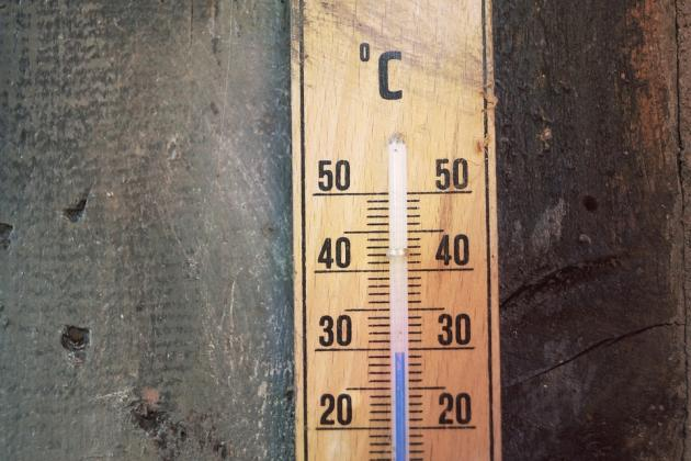 An old thermometer on a wooden wall